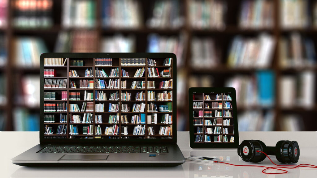 Books on shelves, laptop, tablet, and audio player